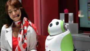 A woman smiles at a robot