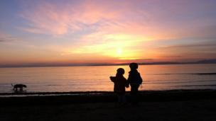Children and dog at sunset