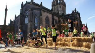Runner takes a tumble jumping over hay bales