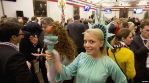 A woman dressed as the Statue of Liberty poses for photographs during an election party at the US Embassy in London
