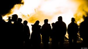 People in front of a bonfire