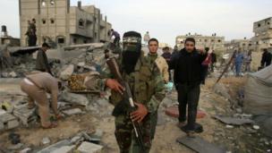 A Hamas militant walks through the debris-strewn streets of Gaza City