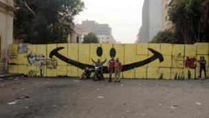 Men pose in front of graffiti on Qasr al-Aini Street, Cairo