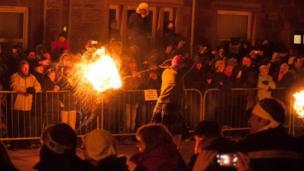 Crowds watch man swinging a fireball
