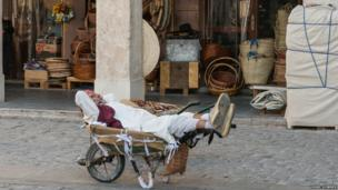 A market porter takes a nap during the mid-day break in the wheel barrow he uses to ferry people's shopping about.