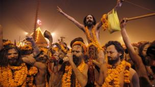 Naked Hindu holy men or Naga sadhus leave from their camp for a dip at Sangam, the confluence of the Rivers Ganges, Yamuna and mythical Saraswati on the first day of the Kumbh Mela
