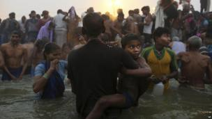 An Indian Hindu boy is held by his father as they go for a dip at Sangam, the confluence of the rivers Ganges, Yamuna and mythical Saraswati, during the royal bath on Makar Sankranti at the start of the Kumbh Mela