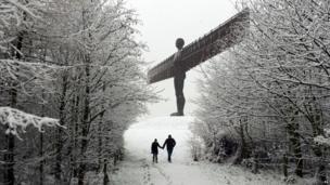 A couple walk through the snow towards the Angel of the North statue near Gateshead