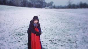 A boy stood on a snowy hill.