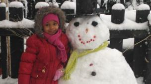 A girl with her snowman. It is wearing a top hat.