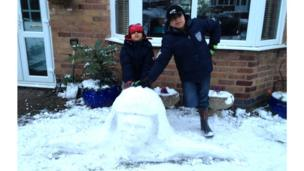 Two boys next to a snow sculpture of a head