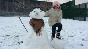 A girl with her snowman.