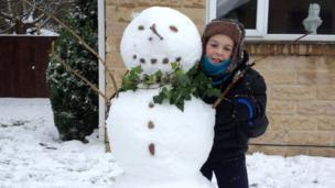 A boy with his snowman.