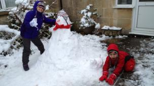 Two children with their snowman.