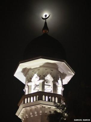 Shot of full moon eclipsed by mosque minaret in Penang, Malaysia. Photo: Samuel Ramos