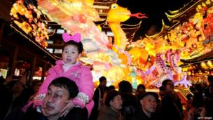 A girl on her father's shoulders in front of a giant dragon lantern in Shanghai