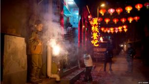 A boy holds a sparkler in an alleyway in Beijing while another covers his ears.