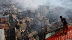 A resident looks at homes destroyed by a fire in Manila