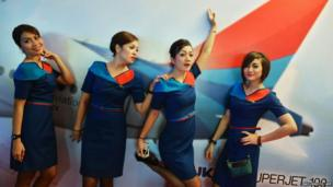 "Flight attendants of Sky aviation pose for photos in front of a poster of the airline company""s new aircraft, the Sukhoi Superjet 100, during the launching ceremony at Halim Airport in Jakarta"