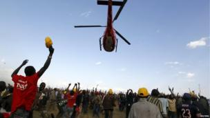 Supporters of Kenya's Deputy Prime Minister and presidential candidate Uhuru Kenyatta cheer as he leaves on a helicopter after a campaign rally in the Rift Valley town of Suswa, about 70 km (43 miles) west of the capital Nairobi, on 27 February 2013