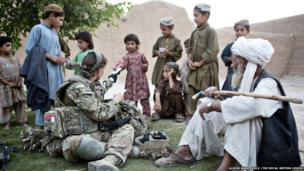 Photograph showing Captain Anna Crossley speaking Pashto in a Helmand compound