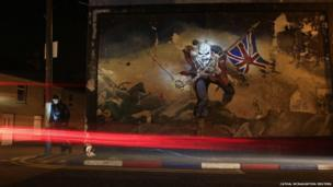 A man checks his mobile phone beside a loyalist paramilitary mural in the Waterside area of Derry