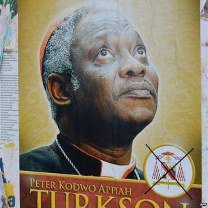 A fake electoral placard, featuring Ghana's Cardinal Peter Turkson, is displayed in front of the Santa Maria Maggiore basilica in Rome on 1 March 2013