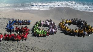Primary schoolchildren from Anguilla pose on the beach at Crocus Bay