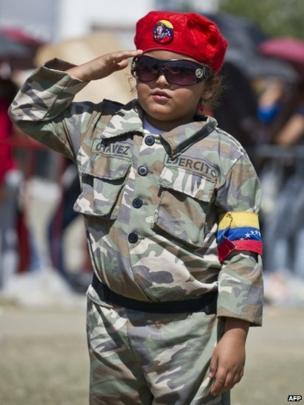 A little girl wearing battledress outside Hugo Chavez's funeral in Caracas on 8/3/13
