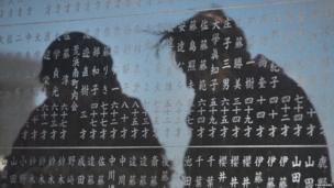 Two women are reflected on a monument on which names of tsunami victims are carved