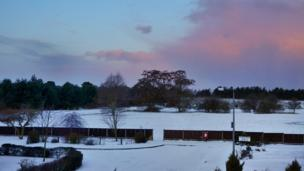 Snow covered fields and driveway. Above are pink and purple clouds in a blue sky.