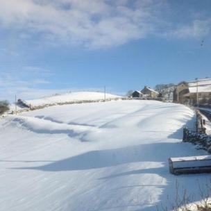 Fields covered in snow. Houses nearby also have snow on them. Blue sky and cloud above.