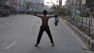 A Bangladeshi opposition activist gestures to police