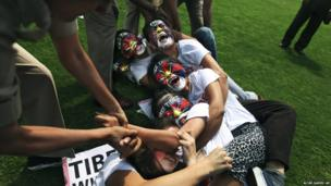 Indian policewomen try to break a human chain formed by exiled Tibetan women