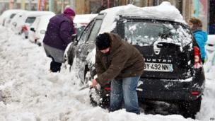 A family clear snow from their car in Cherbourg, France (12 March 2013)