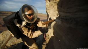 Melissa Battler, a geologist and commander of Crew 125 EuroMoonMars B mission, collects geologic samples for study at the Mars Desert Research Station (MDRS) in the Utah desert