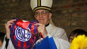 Argentine Cardinal Jorge Bergoglio poses with a jersey from the San Lorenzo football club