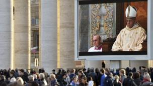 Faithful stand on St Peter's square to watch the first mass by Pope Francis. 14 March 2013