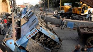 Lebanese policemen inspect the wreckage of a bus that overturned in an accident in Kahale, east Beirut