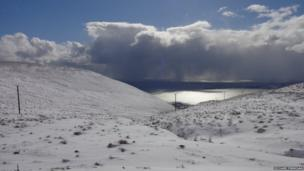 Snow covered hills and distant storm