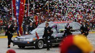 Guards run next to the hearse carrying Hugo Chavez