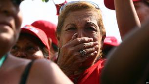 Mourner watches Hugo Chavez's casket pass by. 15 March 2013