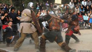 Men wearing traditional medieval costumes fight as they attend a medieval fair in Concepcion