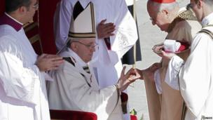 The Fisherman's Ring is placed on the finger of Pope Francis by Cardinal Angelo Sodano (R), Dean of the College of Cardinals