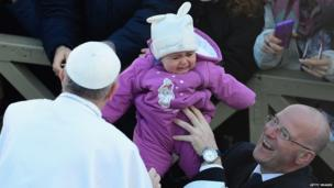 Pope Francis reaches out to touch a child in St Peter's Square