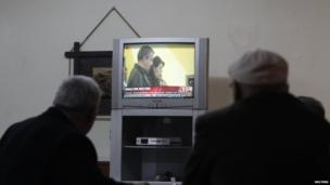 People look at a television screen as pro-Kurdish politicians Sirri Sureyya Onder and Pelvin Buldan read Ocalan's statement, at a coffee shop in Istanbul