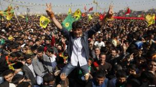 Demonstrators gesture and hold Kurdish flags during a gathering to celebrate Newroz in the Turkish city of Diyarbakir.