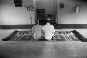 Men sit for evening prayers at the village mosque.
