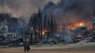 Residents walk past buildings burning in riot-hit Meiktila, central Burma, on 21 March 2013