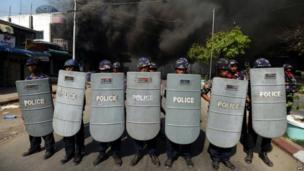 Policemen form a line as they block access to part of the town where a house is burning in riot-hit Meiktila, central Burma, on 22 March 2013